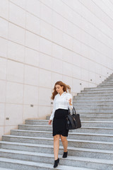 Elegant businesswoman walking down the stairs