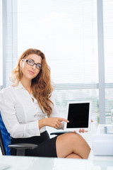 Attractive businesswoman wearing glasses pointing at tablet