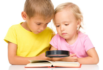 Little girl and boy are reading book