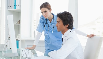 Doctor and surgeon looking at a computer