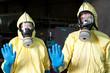 Zwei Helfer in Schutzanzügen warnen vor Ebola