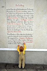Little boy reading text on the wall