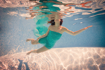 Underwater woman portrait wearing green dress in swimming pool.
