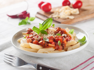 Penne pasta with sauce, cheese and basil, selective focus