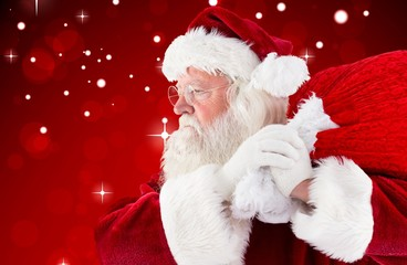 Composite image of santa claus carrying sack
