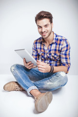 Happy young man holding a tablet pad computer