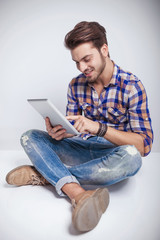young fashion man sitting while using a tablet computer