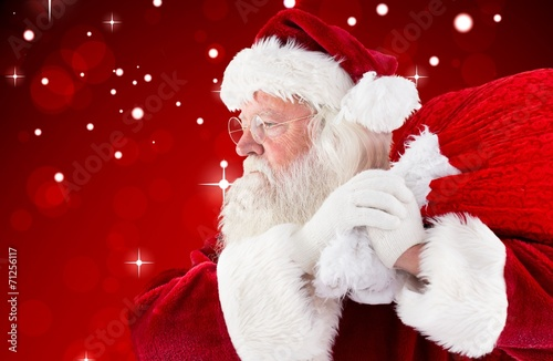canvas print picture Composite image of santa claus carrying sack
