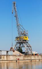 Big industrial harbor crane works on the river coast in Bulgaria
