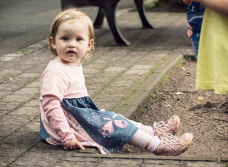 Little blond girl in beautiful dress sitting on the ground