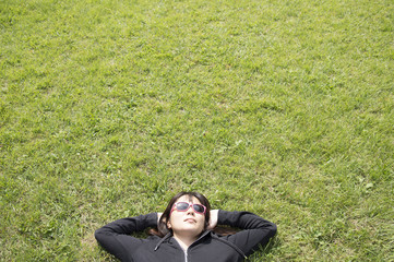 Young woman lying down in the grass