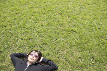 Women who are sunbathing are lying down in the grass