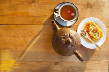 Composition with tea in cup and teapot  on table