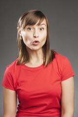 Emotionen: Schockiert. Junge Frau in rotem Shirt