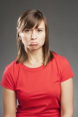 Emotionen: Traurig. Junge Frau in rotem Shirt
