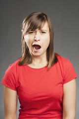 Emotionen: Müde, gähnend. Junge Frau in rotem Shirt