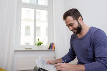 lächelnder mann liest anzeigen in tageszeitung