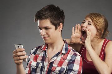 Teenager Paar, Junge mit Smartphone, Mädchen will Aufmerksamkeit