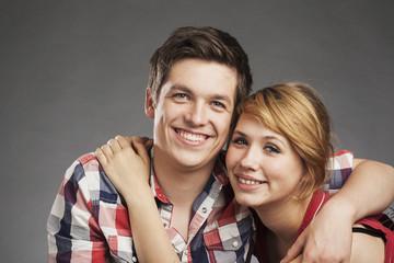 Teenager Paar umarmt sich, freundlicher Blick in die Kamera