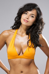 Brünette im gelben Bikini, grauer Hintergrund