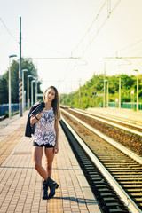 Fashion portrait of young woman outdoors in train station. Filte