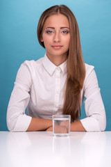 Portrait of girl sitting at the table near a glass with clean wa