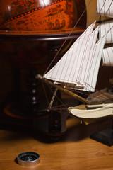 model sailing ship and old globe