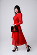 Full length portrait of a woman in red dress on gray background