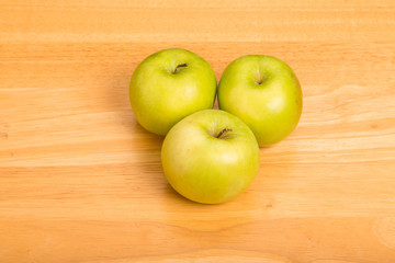 Three Granny Smith Apples on Wood Counter