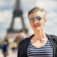 Beautiful young blonde woman portrait in front of the Eiffel Tow