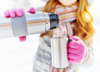 Woman is pouring a hot drink in mug from thermos
