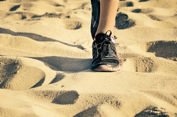 girls feet in sneakers going towards on the sand tinted image
