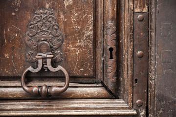 Old rusted knocker on brown wooden door. Paris, France