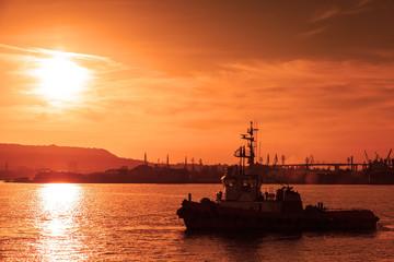 Tug is underway on Black sea at sunset, Varna harbor, Bulgaria