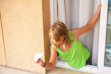 Little blond Caucasian girl with paper plane in the window