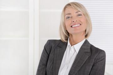 Ältere attraktive blonde Geschäftsfrau in Blazer und Bluse