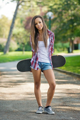 Teenager with skateboard portrait outdoors in the park.
