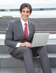 Lachender Geschäftsmann mit schwarzen Haaren und Notebook