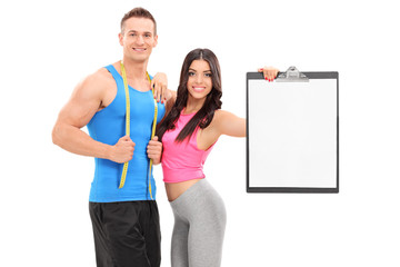Man and woman in sportswear posing with a clipboard