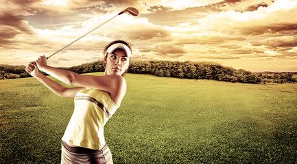 Young female golf player swinging with golf club outdoors