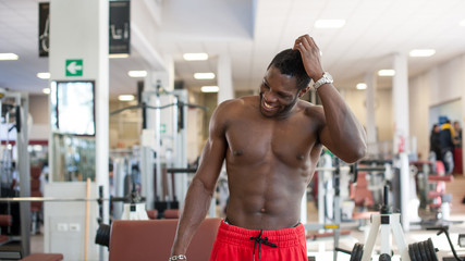 Smiling black man portrait while exercising in the gym.