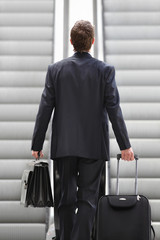 Businessman on escalator with bag and trolley, business trip