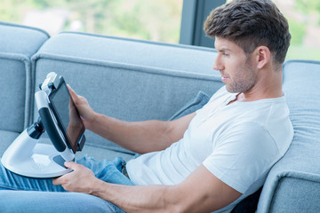 Young Handsome Man on Couch Playing His Gadget