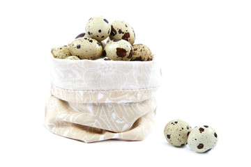 Quail eggs in a canvas bag on white background.