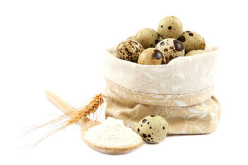 Quail eggs in a canvas bag and flour in a wooden spoon.