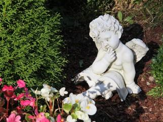 Engel sitzt auf einem Grab und liest