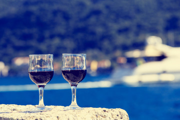 Two glasses of red wine against the seа