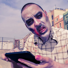 scary zombie using a tablet computer, with a filter effect