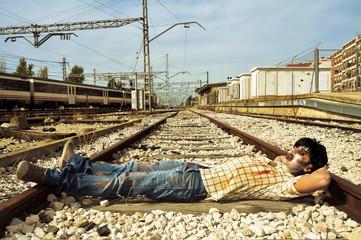 scary zombie taking a nap at abandoned railroad tracks