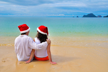 Happy couple in chtistmas hats on tropical beach